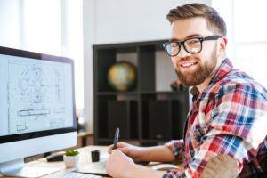 Electrical estimator reviews blueprints on his computer
