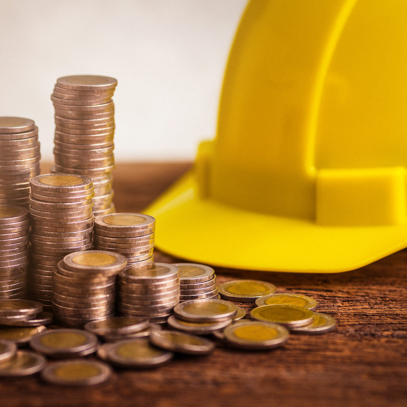 business_financial_ideas_concept_with_coin_stack_with_engineer_yellow_hat_on_wooden.jpeg